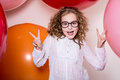 Young girl in glasses showing two fingers victory against the background of large colorful balloons Royalty Free Stock Photo