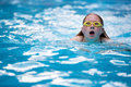 Young girl in goggles and cap swimming breast stroke style the blue water pool Stock Photo