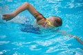 Young girl in goggles and cap swimming crawl stroke style the blue water pool Stock Photo
