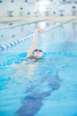 Young girl in goggles swimming back crawl stroke style woman and cap the blue water indoor race pool Royalty Free Stock Photography