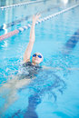 Young girl in goggles swimming back crawl stroke style woman and cap the blue water indoor race pool Royalty Free Stock Photos
