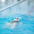 Young girl in goggles swimming back crawl stroke style woman and cap the blue water indoor race pool Stock Photo