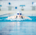 Young girl in goggles swimming butterfly stroke style woman and cap the blue water indoor race pool Royalty Free Stock Photography