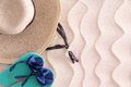 Young girl gone swimming leaving her wide brimmed straw sunhat and slip slops on the golden beach sand with a decorative wavy Royalty Free Stock Photo