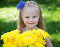 A young girl on a green grass background of holding bouquet of yellow flowers Stock Photography
