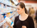 A young girl in a grocery supermarket beautiful woman shopping for milk Stock Images