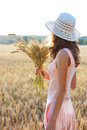 Young girl in the hat and pink dress holding wheat ears in her hand against a background of field concept of abundance Stock Photos