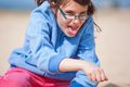 Young girl having fun in glasses with mouth open and tongue out playing a game with her hand Royalty Free Stock Images