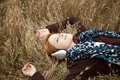 Young girl with headphones lying at field. Stock Images