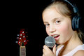 A young girl with headphones singing with a microphone on the black background Royalty Free Stock Photos