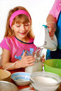 Young girl helping in baking cake Royalty Free Stock Images