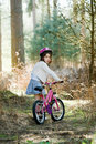 Young Girl with her Bike in the Forest Stock Photography