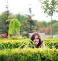 Young girl hiding over bush Stock Photos