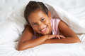 Young girl hiding under duvet in bed smiling to camera Stock Photography