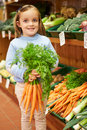 Young girl holding bunch of carrots in farm shop smiling to camera Royalty Free Stock Photo