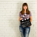 Young girl holding a clapboard against brick wall Royalty Free Stock Images