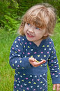 Young girl holding frog this is playing outside and a small green in her hand she s a bit apprehensive about it model is years old Royalty Free Stock Photos