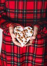 Young girl holding a heart shaped homemade little peanuts cake. Royalty Free Stock Photo