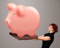 Young girl holding a huge savings piggy bank beautiful Royalty Free Stock Image