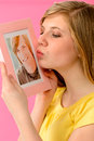 Young girl holding and kissing boyfriends picture a of her love Stock Photography