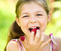 Young girl is holding raspberries on her fingers Royalty Free Stock Photo