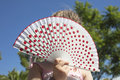 Young girl holding a spanish fan with red dots outdoors white hand held x or x Royalty Free Stock Image