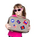 Young girl holding suitcase with stickers from various countries. isolated on white Royalty Free Stock Photo