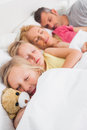 Young girl holding a teddy bear next to her sleeping family in bed Stock Photo