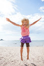 Young girl jumping at beach cute happy in the sand the in summer Stock Photography