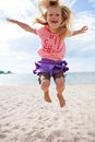 Young girl jumping at beach cute happy in the sand the in summer Stock Image