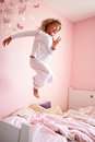 Young girl jumping on her bed at home having fun Stock Photo