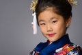 Young girl in kimono on grey a cute japanese wearing a a background Royalty Free Stock Image