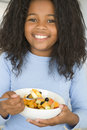 Young girl in kitchen eating bowl of fruit smiling Royalty Free Stock Photos