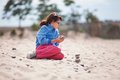 Young girl kneeling on beach wearing spectacles a sandy making a pile of stones Royalty Free Stock Photo