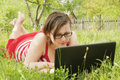 Young girl with laptop outdoors out in the yard laying down a Royalty Free Stock Photo