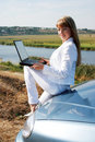 Young girl with laptop sitting on the car Stock Images
