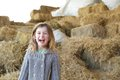 Young girl laughing on farm close up portrait of a with haystacks Royalty Free Stock Image