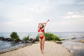 Young girl with ldark hair in red swimsuit posing on the beach Royalty Free Stock Photo
