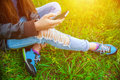 Young girl in leather jacket and ripped jeans sitting on the grass in the park and talking to friends on the phone Royalty Free Stock Photo