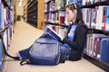 Young girl library reading book asina student sitting and in Royalty Free Stock Photography