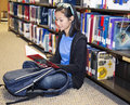 Young girl library reading book asina student sitting and in Royalty Free Stock Photos