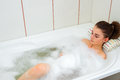 Young girl lies in hot water in the bath with foam Royalty Free Stock Photo