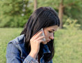 Young girl listening to a call on her mobile beautiful with serious concerned expression she stands outdoors denim jacket park Royalty Free Stock Image