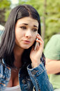 Young girl listening to a call on her mobile beautiful with serious concerned expression she stands outdoors denim jacket park Royalty Free Stock Photos