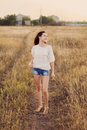 Young girl with long brown hair stay at the meadow, smiling. Royalty Free Stock Photo