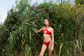Young girl with long dark hair in red swimsuit posing outdoors in the reeds Royalty Free Stock Photo