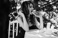 Young girl in a long evening dress is sitting at a white table in the park and eating a hamburger. Black and white photography Royalty Free Stock Photo