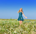 The young girl with a long fair hair in a blue dress costs in the field beautiful happy woman of chamomiles guesses on chamomile Royalty Free Stock Photos