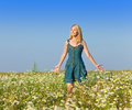 The young girl with a long fair hair in a blue dress costs in the field of camomiles against the blue sky beautiful happy woman Royalty Free Stock Photography