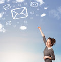 Young girl looking at mail symbol clouds on blue sky casual Royalty Free Stock Photography